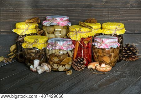Mushrooms Marinaded In Glass Jars. Fermented Mushrooms On Rustic Widen Background. Mushrooms Conserv