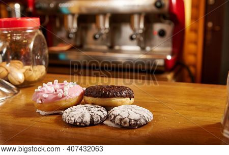 Doughnuts And Brownies On A Wooden Surface Or Table On The Background Of A Coffee Machine At Cafe