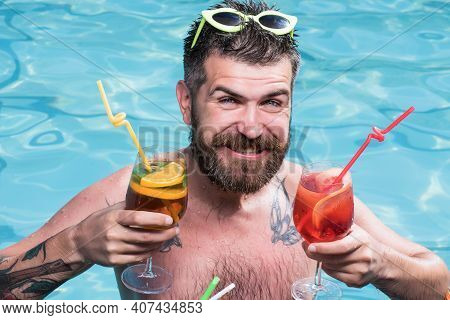 Cocktail Party With Bearded Man In Pool. Guy Swimming And Drink Alcoholic Beverage. Summer Vacation