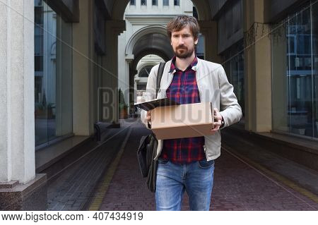 A Fired Man Stands On The Street And Holds His Things After Leaving The Company. Unemployed Man Lost