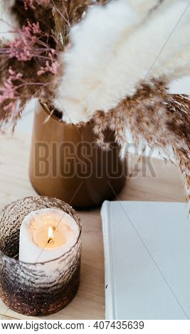 A White Blank With Candlelight, As Decoration In The Room, Is Laying On The Brown Background. Copy S