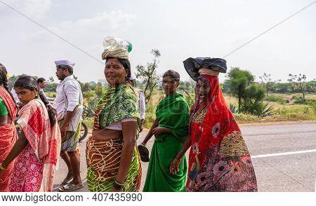 Jamunai, Karnataka, India - November 8, 2013: Women In Colorful Saris And Carrying Stuff On Their He
