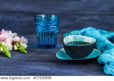 Coffee Cup, A Glass Of Water And Snapdragons Flowers