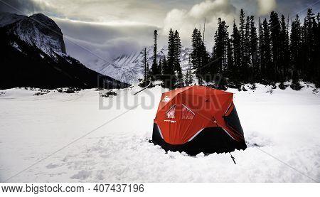 Kananaskis Alberta Canada, February 4 2021: A Eskimo Ice Fishing Tent Sits On The Frozen Kananaskis