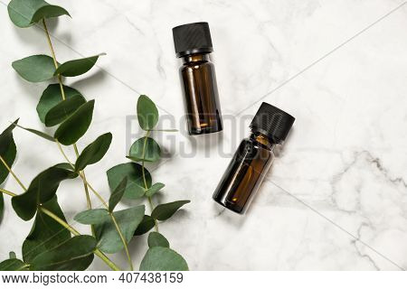 Two Amber Bottles Of Eucalyptus Essential Oil And Fresh Eucalyptus Branch On Marble Background. Natu