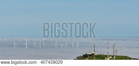 Many Wind Turbines Above A Foggy Valley With Aerials And Antennas On A Hilltop In The Foreground