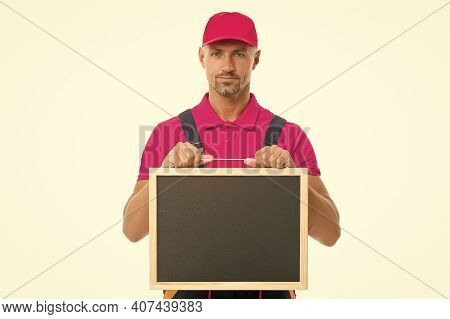 Man In Overall With Empty Board. Place For Copy Space. Announcement Concept. Male Construction Worke