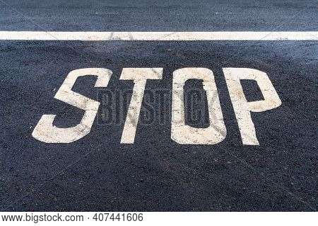 A Blacktop Asphalt Road With A White Line And The Word Stop Written On The Pavement