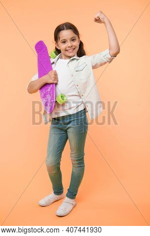 I Can Ride It. Kid Girl Happy Holds Penny Board. Girl Happy Face Carries Penny Board Yellow Backgrou
