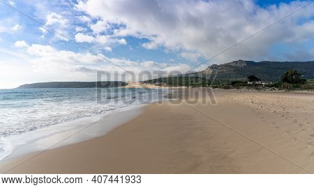 A Peaceful Empty Golden Sand Beach With Waves Rolling In And Pine Forest And A Large Sand Dune In Th