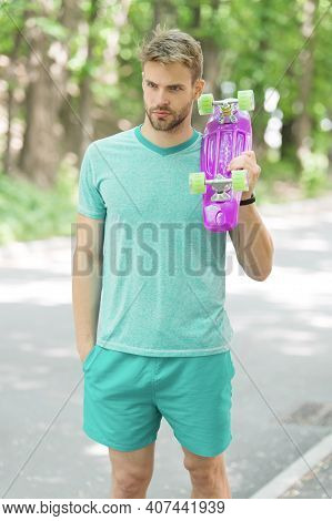 He Will Show His Best In Skateboarding. Guy Carries Penny Board Ready To Ride. Man Serious Face Carr