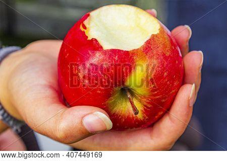 Red Bitten Off Apple In Hand In Norway.