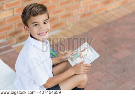 Portrait of smiling caucasian schoolboy using digital tablet on video call with female teacher. Online education staying at home in self isolation during quarantine lockdown.