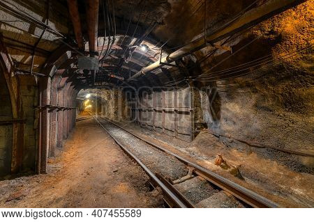 Tunnel Of The Mining Of An Underground Mine. Lots Of Pipelines On The Ceiling And Rail Track For Tro