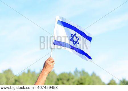 Israeli Flag, Man Hand, Blue Sky, Nature Background.memorial Day-yom Hazikaron, Patriotic Holiday In