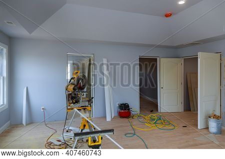 Construction Remodeling Home With Close Up Of Circular Saw Cutting Wood Trim Molding