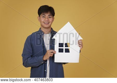 Portrait Of Smiling Happy Cheerful Young Asian Man Dressed Casually With Home House Paper Cutout Iso