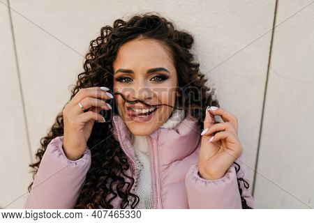 Crafty Smile, Flirty Look And Curly Dark Curl Of Hair Attached To The Face Of A Girl In A Warm Jacke