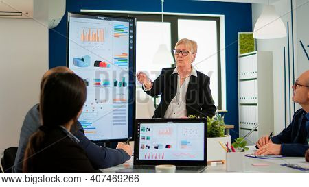 Elderly Project Manager Pointing At Desktop Presenting Statistical Data, Briefing Diverse Group Of E
