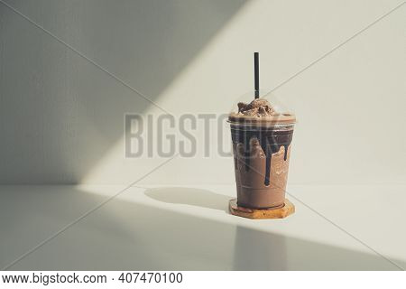 Iced Chocolate Shakes Cream In Plastic Cup On Wood Table At Cafe. Cold Cocoa Smoothie In Coffee Shop