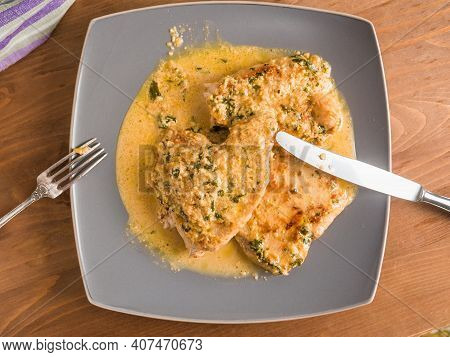 Fried Turkey Breast Steaks With Creamy Sauce On A Large Plate With Fork And Knife On A Wooden Table