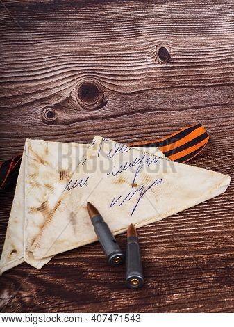 Two Cartridges, Bullet Casings On A Wooden Background, Letters About The War The St. George Ribbon A