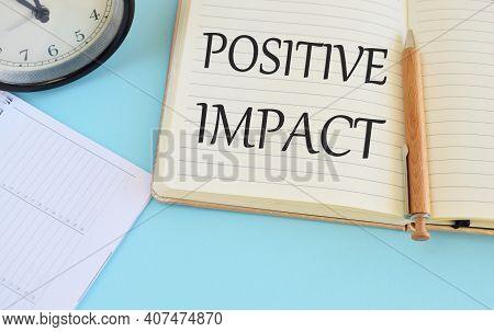 Positive Impact Text Written In Notebook, Light Blue Background, Business Concept