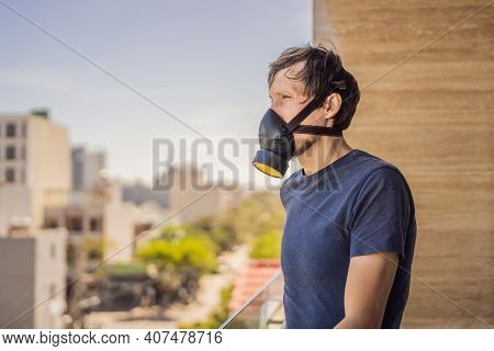 Close Up Portrait Of Young Man In Respirator Mask Against The Background Of The City. Man Puts On A