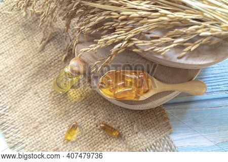 Bottles Of Rice Bran Oil With Rice Bran Oil Capsules On A Wooden Cutting Board With Dry Ear Of Rice