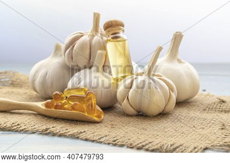 Capsule Garlic Oil In Wooden Spoon With Stethoscope And Fresh Garlic Background, The Benefit Of Garl