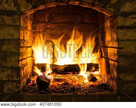 Burning Firewood In Fire-box Of Fireplace In Country Cottage. Orange Light Of Flame And Embers Warmt