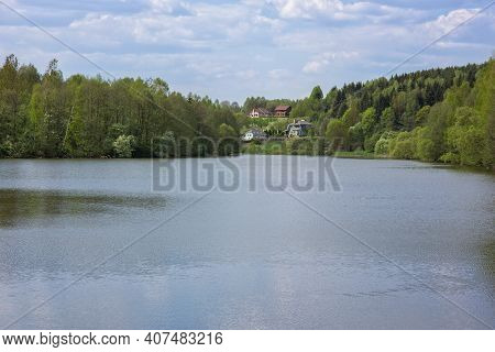 Big Forest Lake. Hilly Shores Overgrown With Forest. Several Cottages On The Far Shore. Cloudy Blue