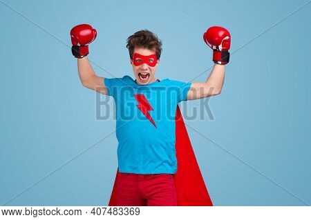 Enraged Young Guy In Superhero Costume And Boxing Gloves Raising Arms And Screaming During Fight Aga