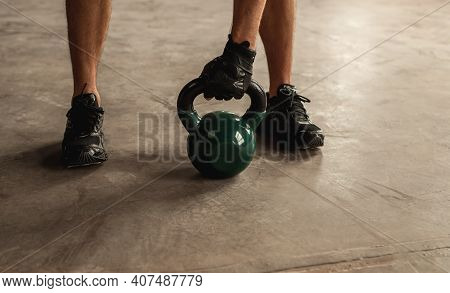 Unrecognizable Male Athlete Grasping Heavy Kettlebell On Concrete Floor During Weightlifting Workout