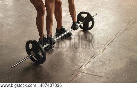 High Angle Of Anonymous Male Athlete Lifting Barbell From Floor During Weightlifting Workout In Gym