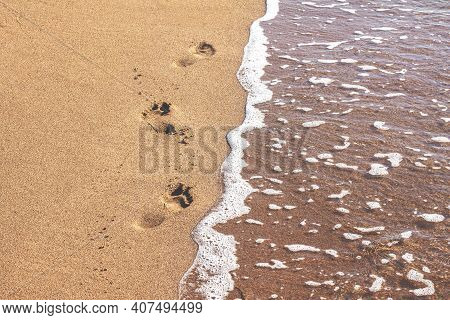 Deep Footprints Of Human Bare Feet On A Beach With Smooth Brown Wet Sand To The Left Of The Sea With