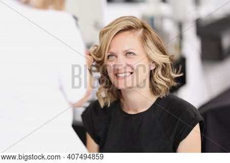 Portrait Of Smiling Woman Who Has Her Hair Done From Curls. Evening Hairstyles Concept