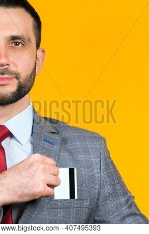 Portrait Of A Man In A Business Suit Who Puts A Bank Card In His Breast Pocket On A Yellow Backgroun