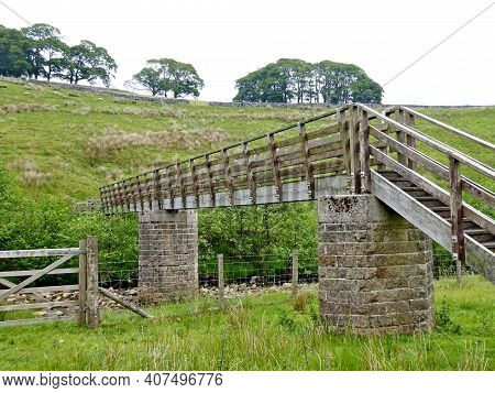 A Wooden Footbridge In The Forest Of Bowland