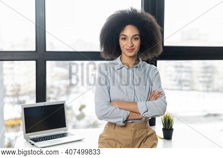 Successful Confident Young Mixed-race Female Entrepreneur Or A Businesswoman With Afro Hairstyle In