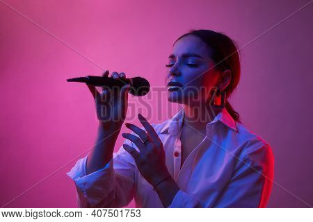 Female Singer In Neon Light. Girl In White Shirt With Microphone. Concept Of Art, Human Emotions, Mu