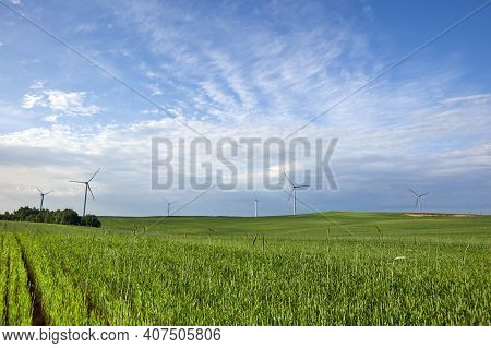 Wind Turbine On The Green Grass Over The Blue Clouded Sky. Wind Turbine - Renewable Energy Source.