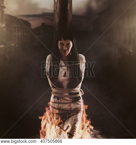 Medieval Witch Is Tied To A Wooden Post And Burns At The Stake And Smile