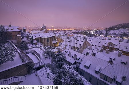 Cityscape Of Prague In Winter. View Of Snowy Roofs Of Lesser Town At Night.