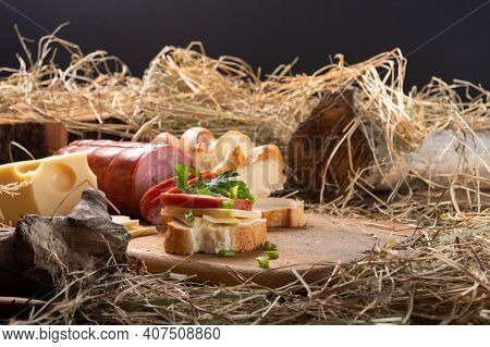 A Snack Among The Hay And Firewood. Bread, Firewood And Hay. Rustic Stele.