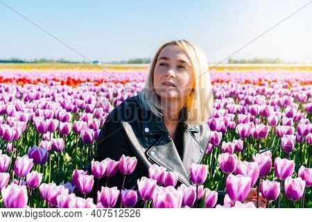 Beautiful Woman With Blond Hair Standing In Colorful Tulip Flower Fields In Amsterdam Region, Hollan