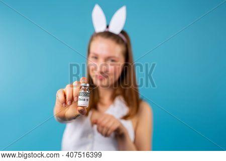 Coronavirus Vaccination. Caucasian Blonde Girl Wearing Bunny Ears In Background, Holding Focused Amp