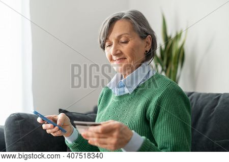 Senior Mature Businesswoman Holding A Cellphone And Checking Clarifying Credit Card Number To Make O