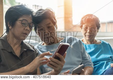 Aging Society Concept With Asian Elderly Senior Adult Women Sisters Using Mobile Digital Smart Phone