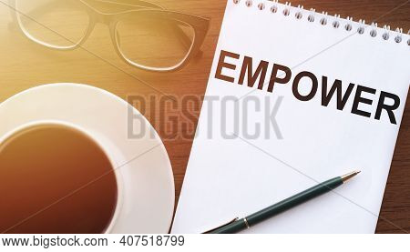 Empower - Text On Paper With Cup Of Coffee And Glasses On Wooden Background In Sinlight.